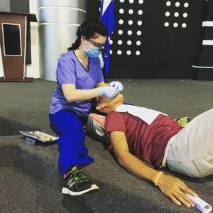 female dentist treating male patient on floor