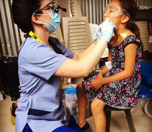 Female dentist checking childs teeth