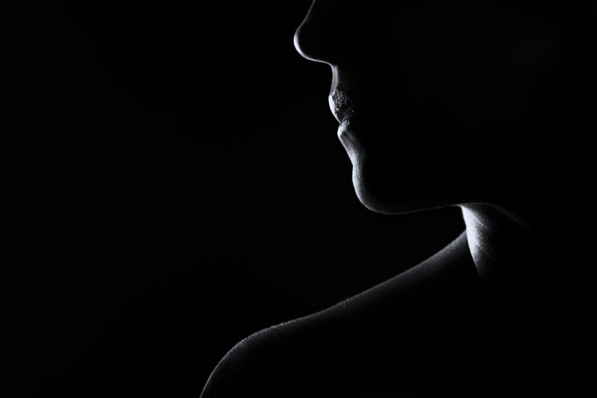 Silhouette of a woman face in black and white rim lighting dental