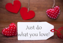 Label With English Quote Just Do What You Love. White Label With Red Textile Hearts. Retro Brown Wooden Background.