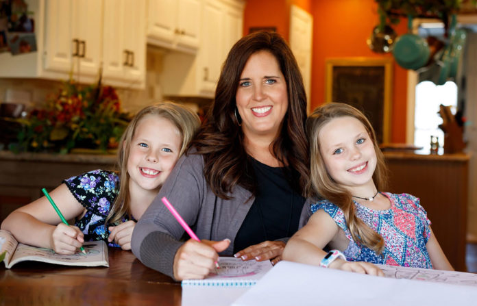 A photo of Dr Jill Wade and her 2 daughters making a list after their house flood