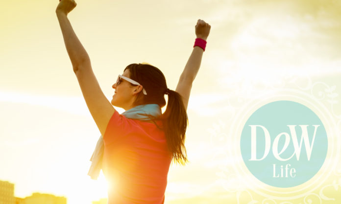 woman with arms raised apparently victorious in a race or other healthy pursuit