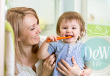 mom holding baby brushing its own teeth