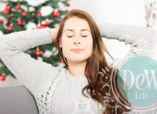 woman relaxing in front of holiday Christmas tree for stress relief