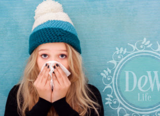 girl in winter hat with tissue blowing nose in flu season