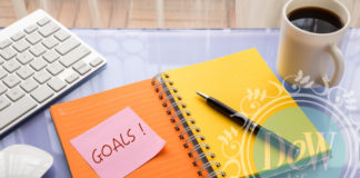 a planner calendar diary to help achieve goals is laid out with pen on desk beside a cup of black coffee