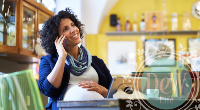 pregnant mom sitting at a desk with computer talking on cell phone embracing a new opportunity